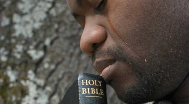 man in tears with Bible