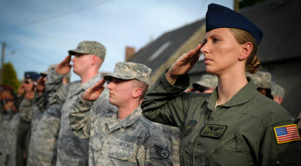 U.S. Air Force Airmen salute as the national anthems of America and France are played during a ceremony in the town of Picauville, France on the 70th Anniversary of D-Day, June 6, 2014.